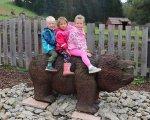 děti sedí na medvědovi